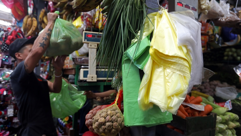 A vendor holds a green plastic bag at a market in Lima, Peru