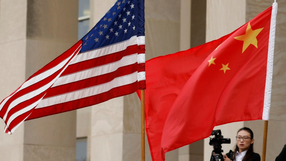 US and Chinese flags are showing flying with a photographer in the background at the Pentagon in Arlington, VA.