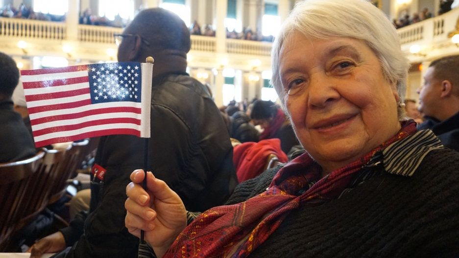 a close up on Natalia Malkes waving a small flag during hercitizenship ceremony