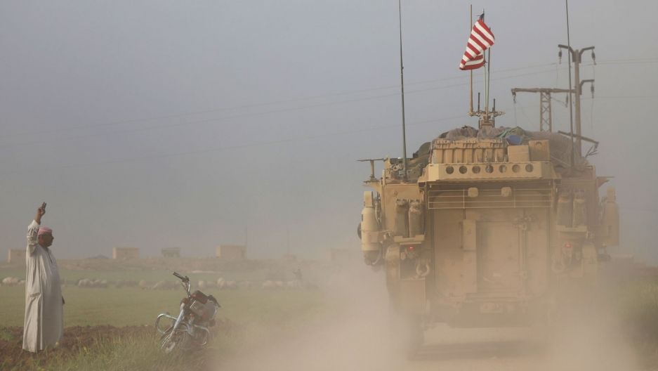 A man is shown waving to a large MRAP US military vehicle with a dust cloud coming up from the truck.