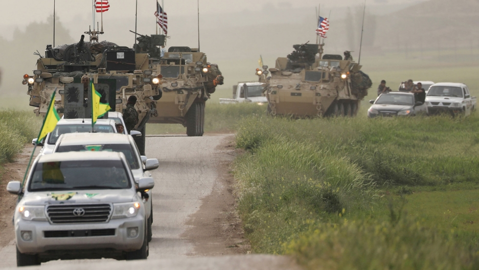 Kurdish fighters driving Toyota SUVs with green and yellow flags on top are shown driving in head of US military MRAP vehicles.