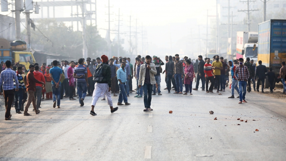 Garment workers block a road as they protest for higher wages.