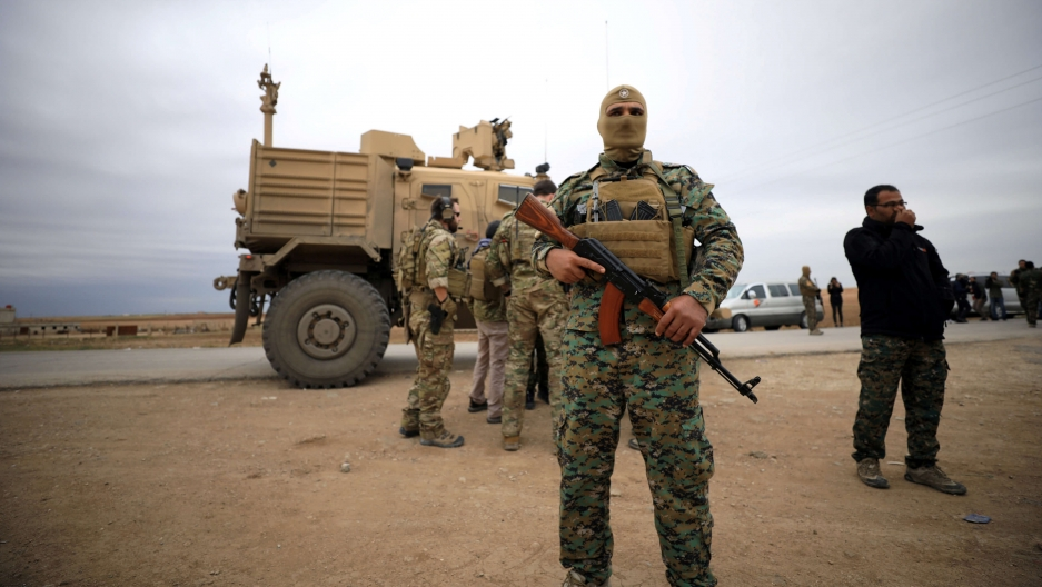 A masked Syria fighter stands in front of an American tank and some troops.