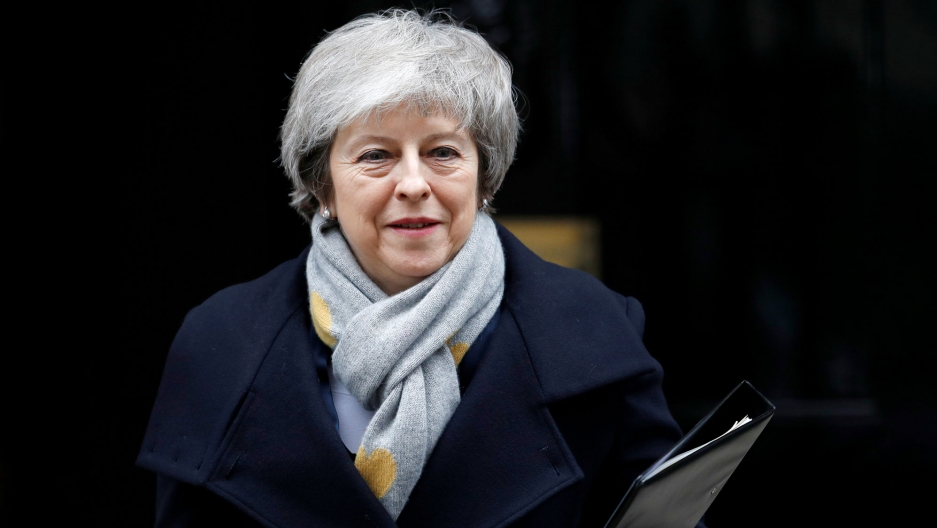 Britain's Prime Minister Theresa May is shown wearing a grey scarf and blue overcoat with a binder in her left hand.