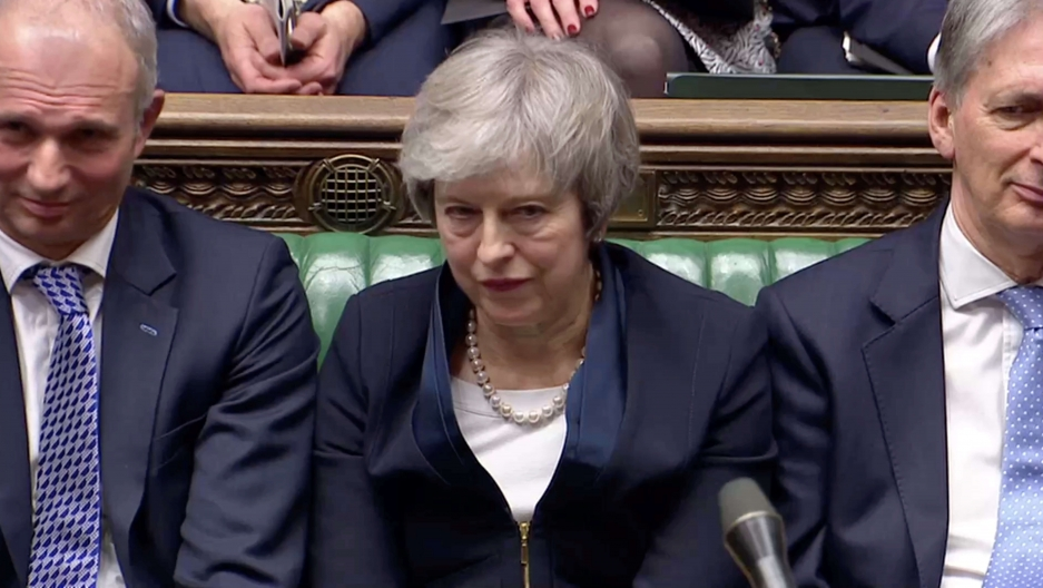 Prime Minister Theresa May sits down in Parliament with a grimace on her face