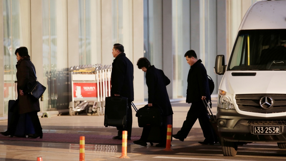 North Korean officials are shown walking from a white van with luggage at the international airport in Beijing, China.