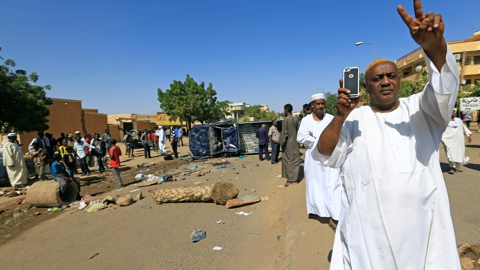 A Sudanese man makes a peace sign with his hands