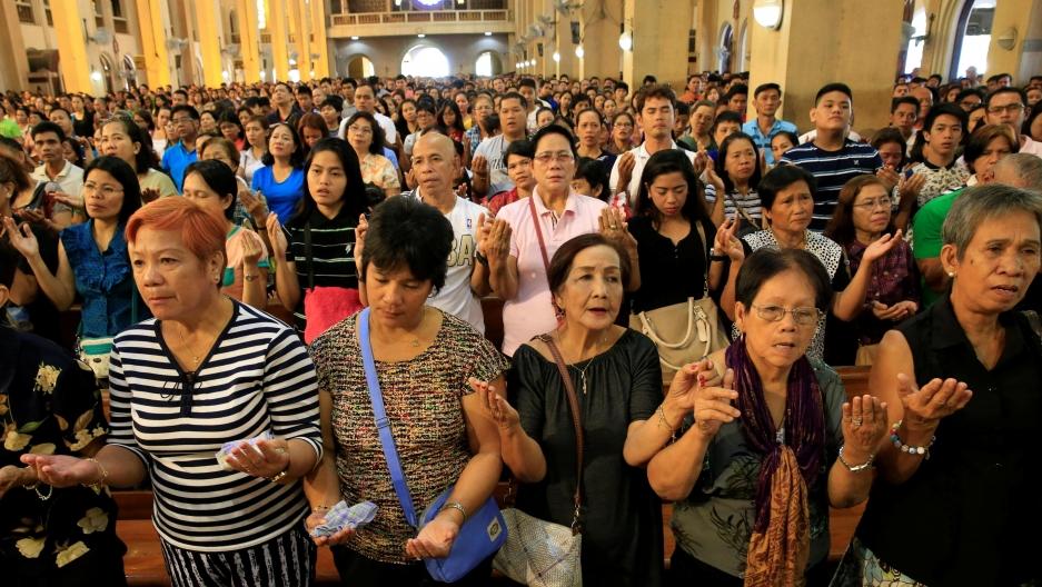 dozens of Filipino church goers praying