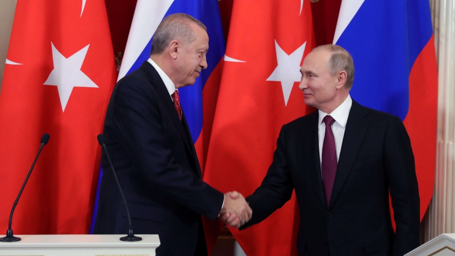 Russian President Vladimir Putin and his Turkish counterpart Tayyip Erdogan shake hands in front of their nations' flags