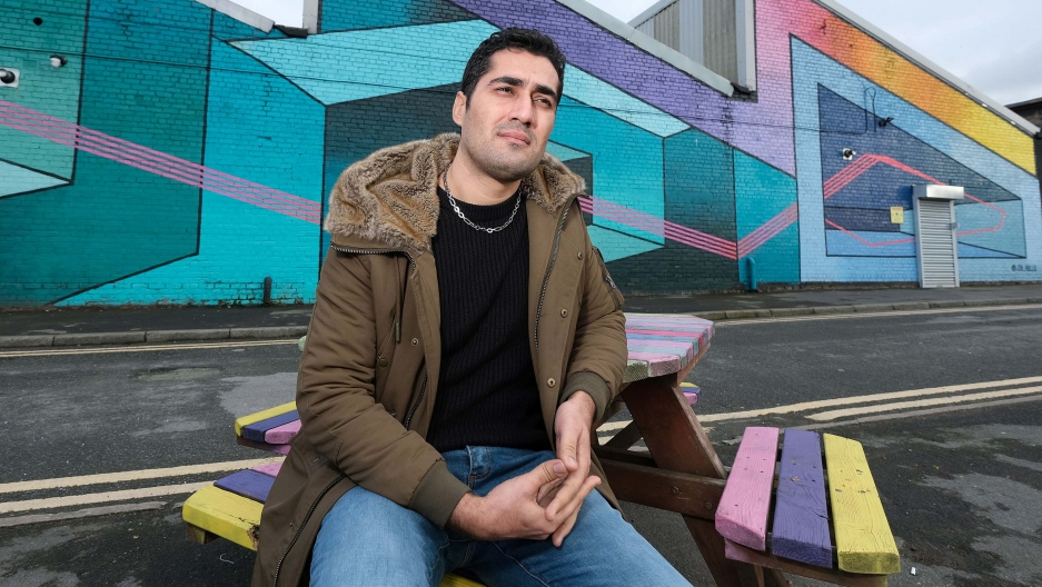 A man with short brown hair sits in front of a colorful geometric mural