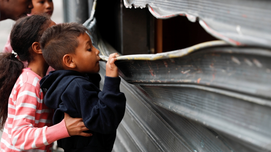 a small boy looks through the bent metal of a garage door