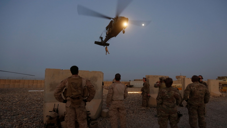 US troops are shown in the near ground with a helicopter flying in the background.