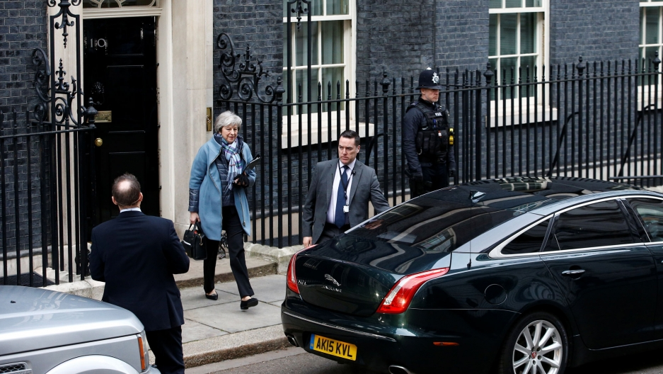 Britain's Prime Minister Theresa May is shown in a blue jacket and scarf walking out of 10 Downing Street to a car.