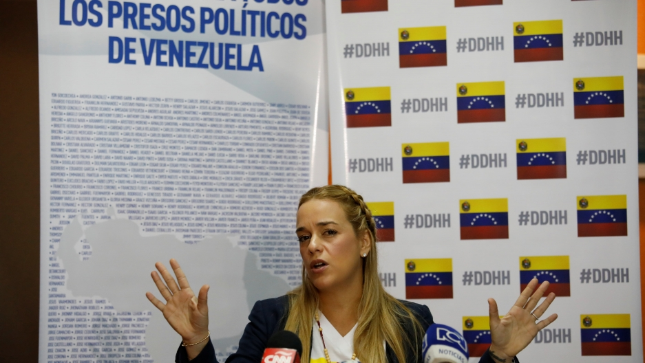 "A blonde Lilian Tintori, speaks during a meeting with a banner in the background that reads: ""Freedom for all the political prisoners in Venezuela."""