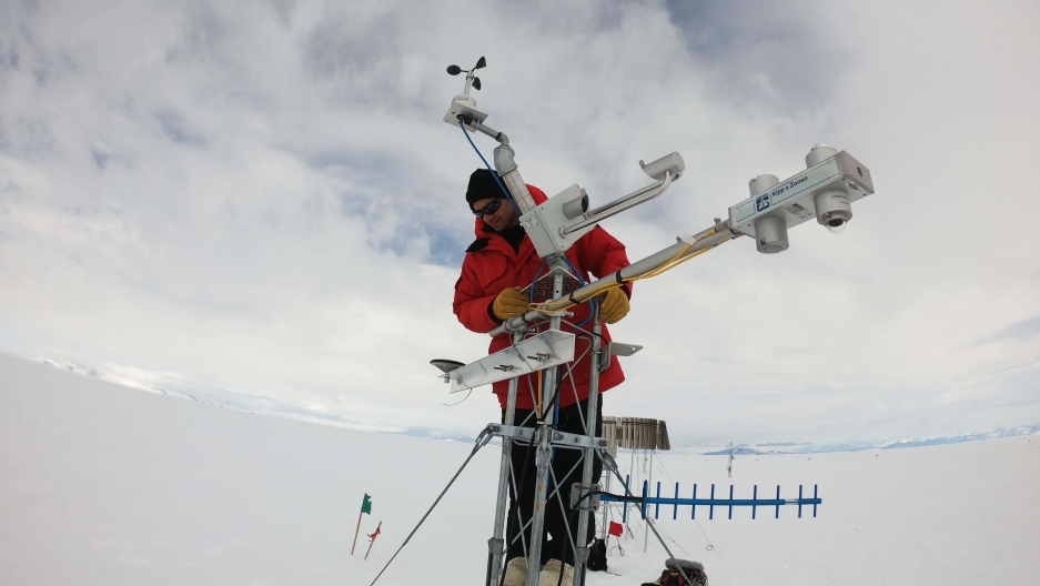 a man in a red coat stands on top of a large research instrument