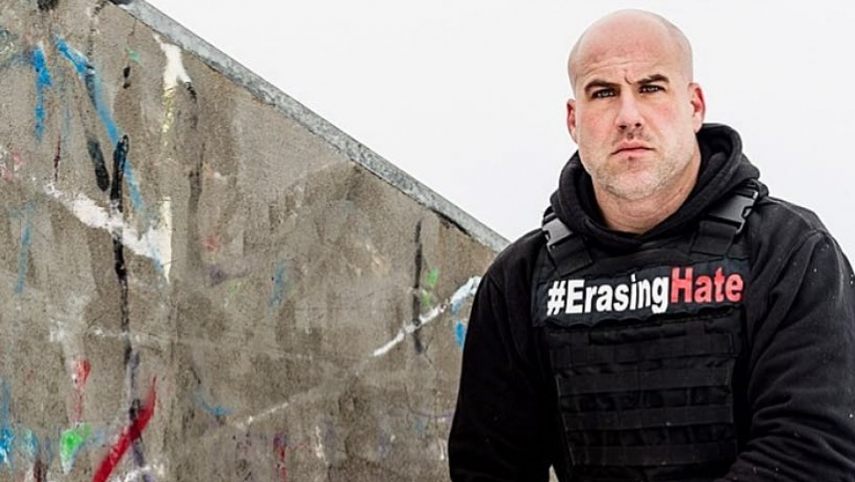 "a bald man crouches down next to a graffiti-covered stone. he wears a vest that says ""erase the hate"""