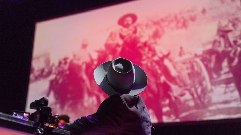 a performer wearing a hat looks at the giant projection of Pancho Villa on the stage film screen
