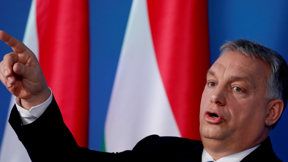 Orban points his finger with red and white flags behind him.