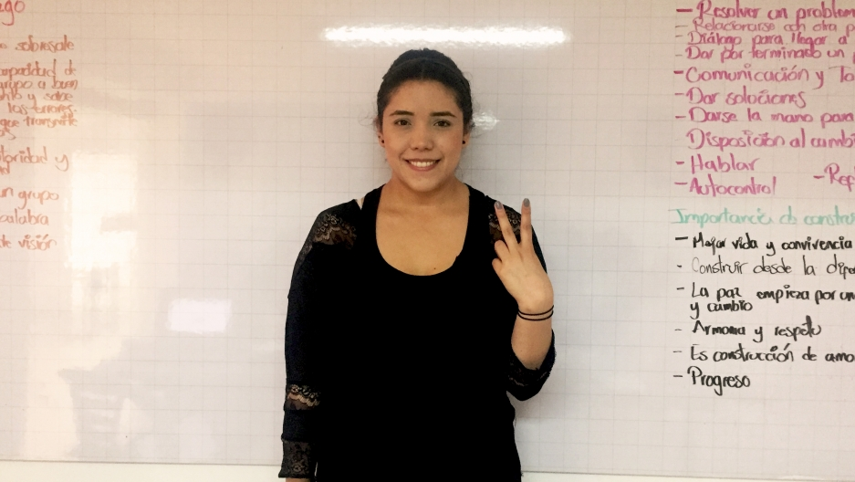 A young woman with dark hair gives the peace sign inside a prison.