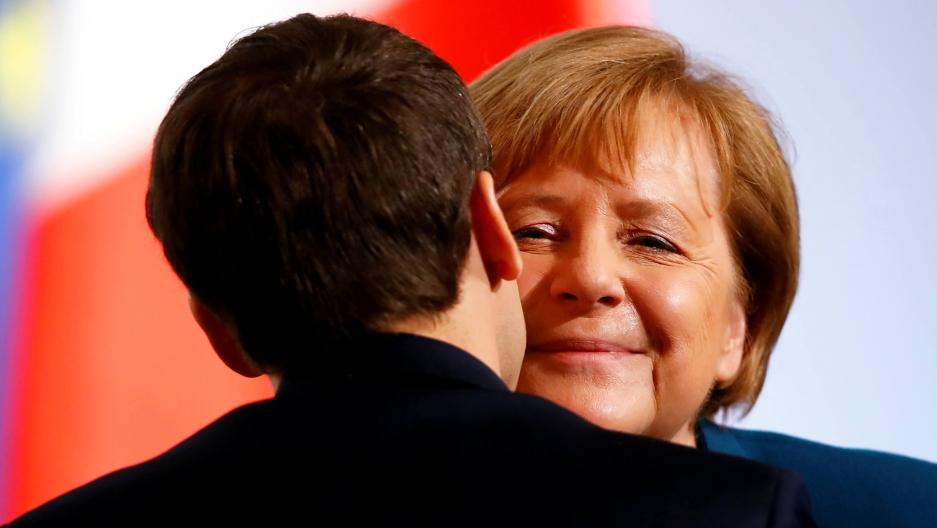 Macron hugs Merkel.