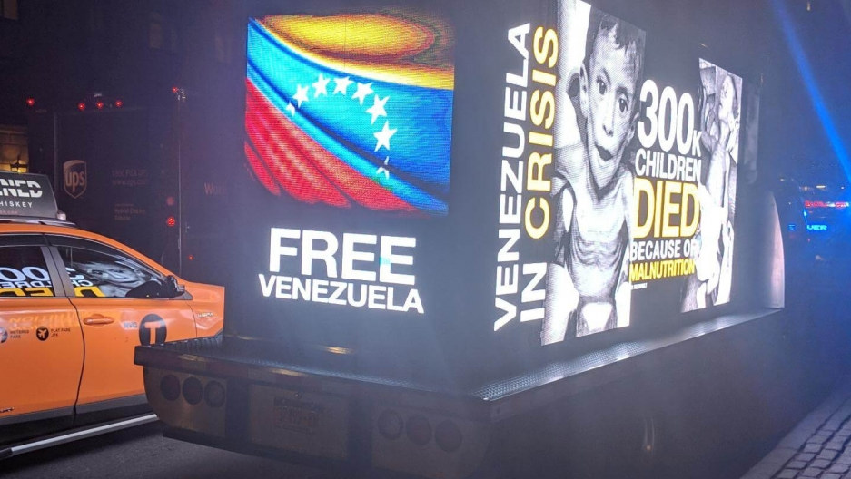 A glowing billboard on a mobile truck says Free Venezuela.