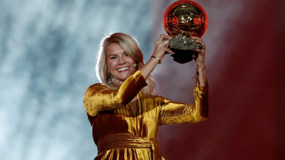 Ada Hegerberg wears a gold dress while holding a gold trophy over her head