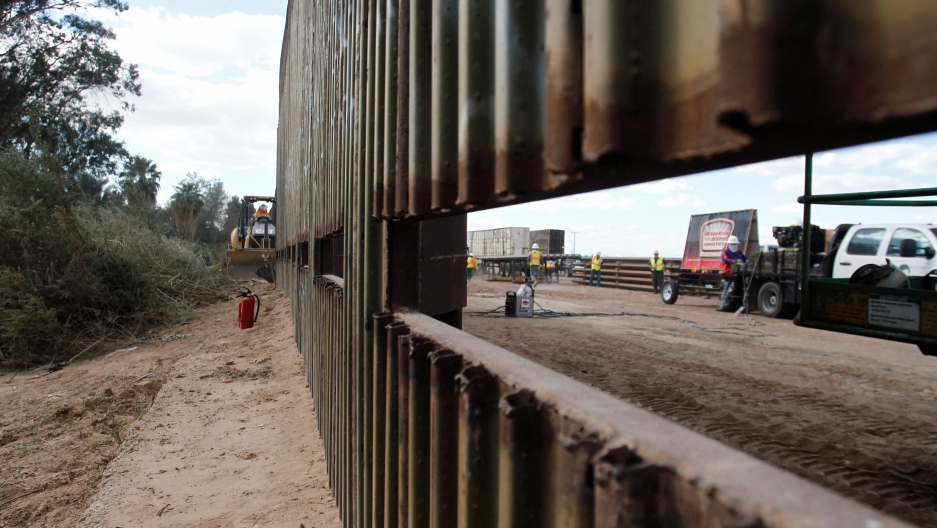 a portion of the US Mexico border. a whole in the wall allows you to see the other side