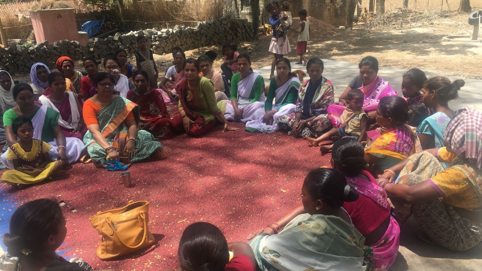 women wearing colorful saris gather in a circle.