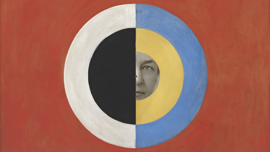 "Portrait of Hilma af Klint, circa 1910s, behind one of her paintings, ""Group IX/SUW, The Swan, No. 17 (Grupp IX/SUW, Svanen, nr 17),"" 1915 from ""The SUW/UW Series (Serie SUW/UW)."""
