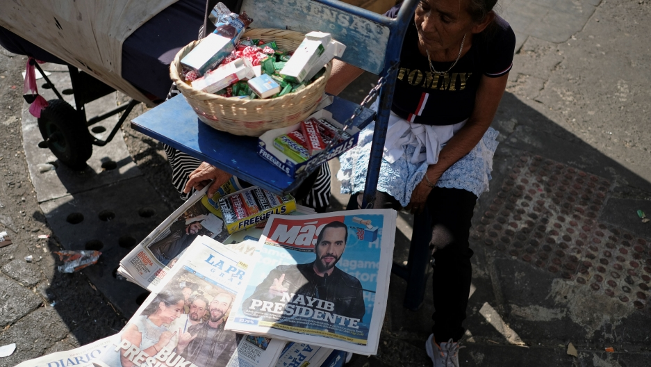 A woman sits on the street with piles of newspapers and gum for sale. The newspapers have the news that Nayib Bukele will be the next president of El Salvador.