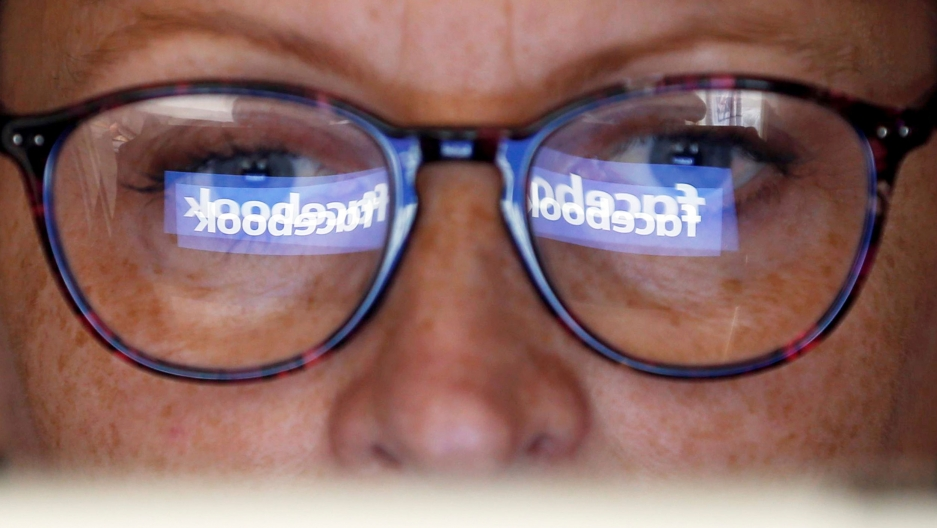 The Facebook logo is reflected in the lenses of a woman's glasses