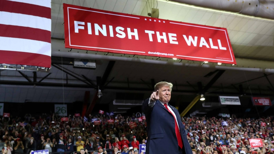 "Donald Trump stands in an arena with a banner overhead that reads ""Finish the wall."""