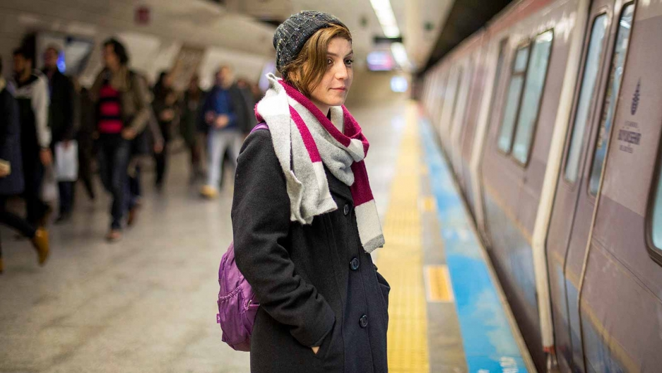A woman wearing a hat stands on a subway platform