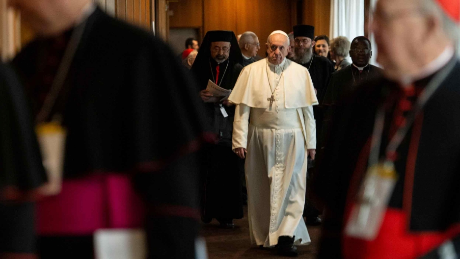 Pope Francis walks through a group of other clergy members