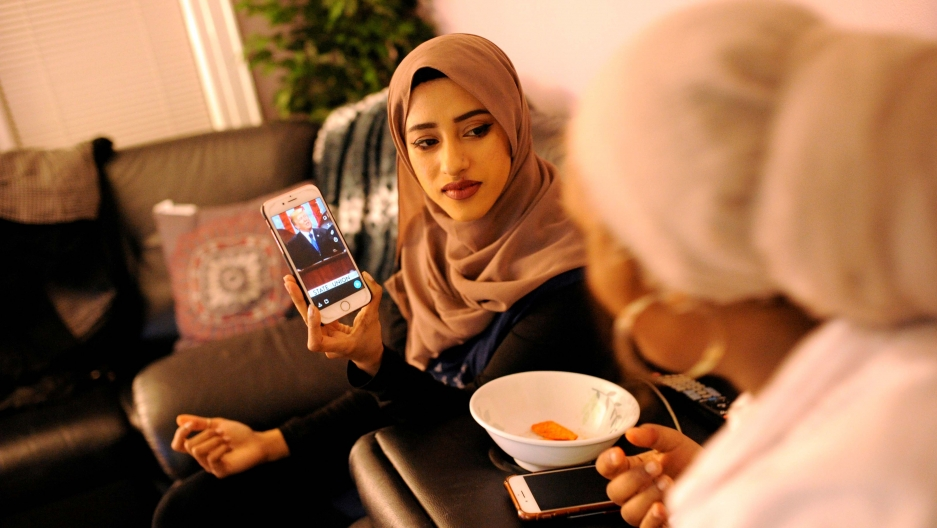 A young woman in a hijab shows her phone screen to another young woman whose back is turned to the camera. On the phone is Donald Trump.