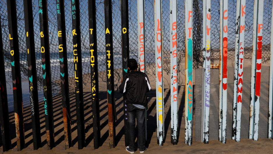 A boy looks through the slats of the US-Mexico border fence at Friendship Park in Tijuana, Mexico.