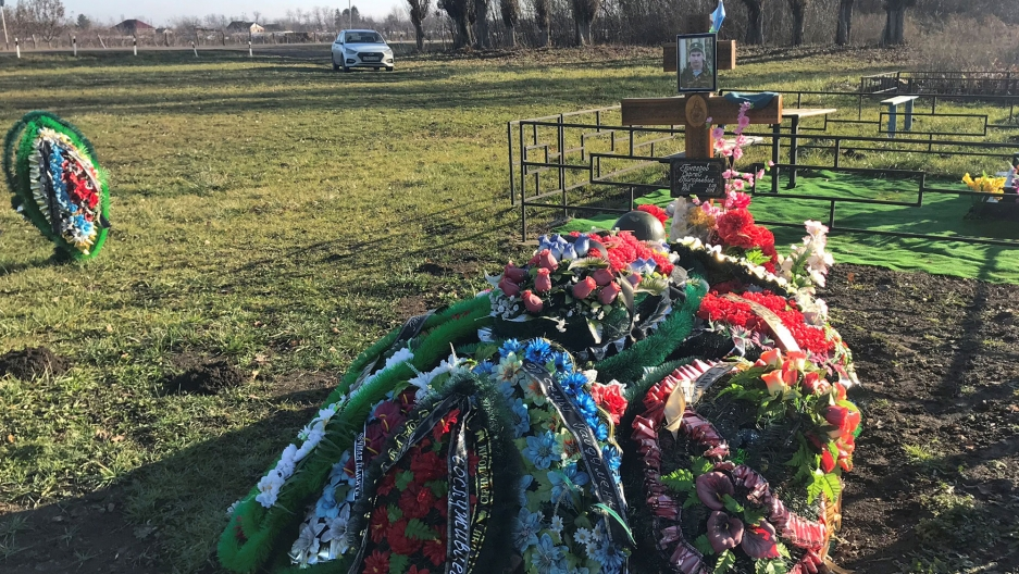 The grave of Russian private military contractor Sergei Gancherov is shown adorned with flowers and his photograph on a cross.