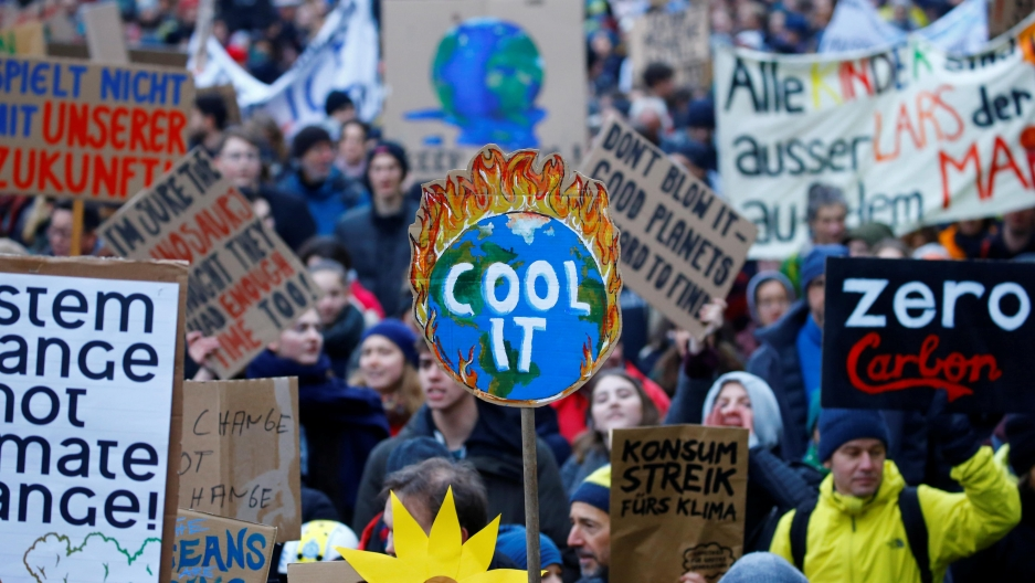 "a large crowd of people marching, a sign that read ""cool it"" is the most prominent"