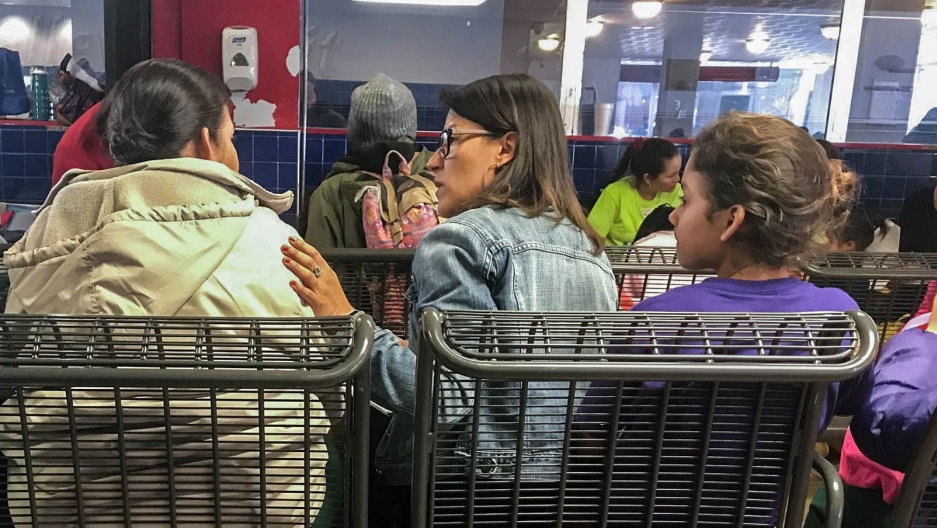 Alicia Cruz, in the center of the photograph, is shown wearing a jean jacket and putting her left hand on the shoulder of the woman next to her.