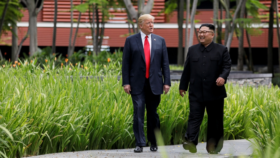 US President Donald Trump is shown wearing a suit and red tie, walking with North Korea's leader Kim Jong-un, wearing an all black outfit surrounded by greenery.