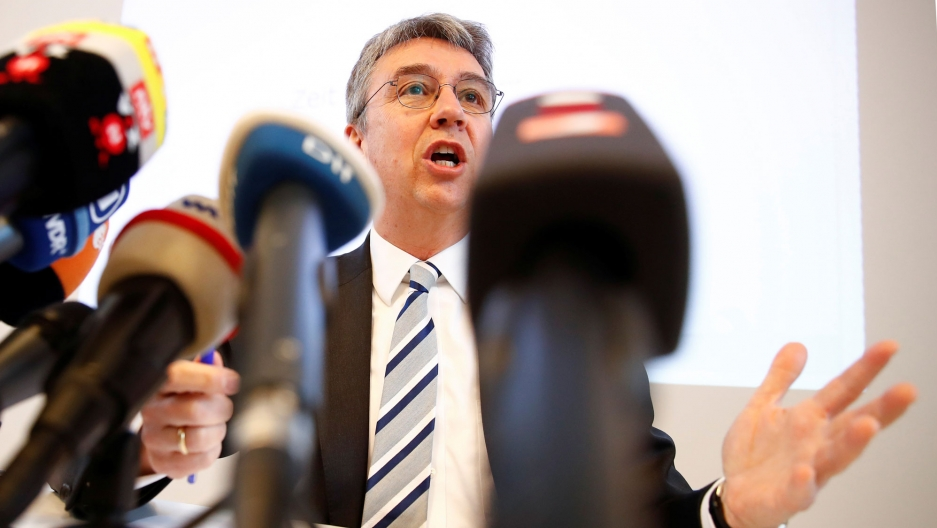 Andreas Mundt is shown behind several microphones wearing a suit and striped tie.