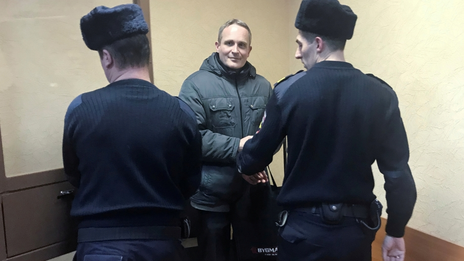 A Danish man seen with two Russian police in an office.
