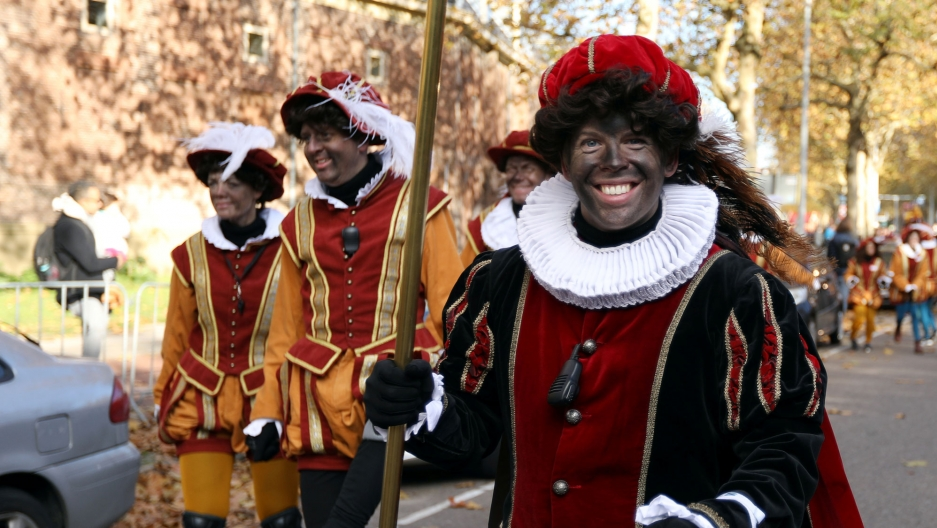 Parade participants in Amsterdam, Netherlands, are shown in jester attire and in blackface.