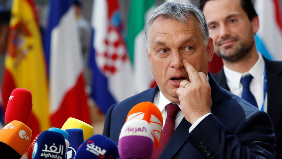 Hungarian Prime Minister Viktor Orbán stands in front of several flags while speaking into several media microphones