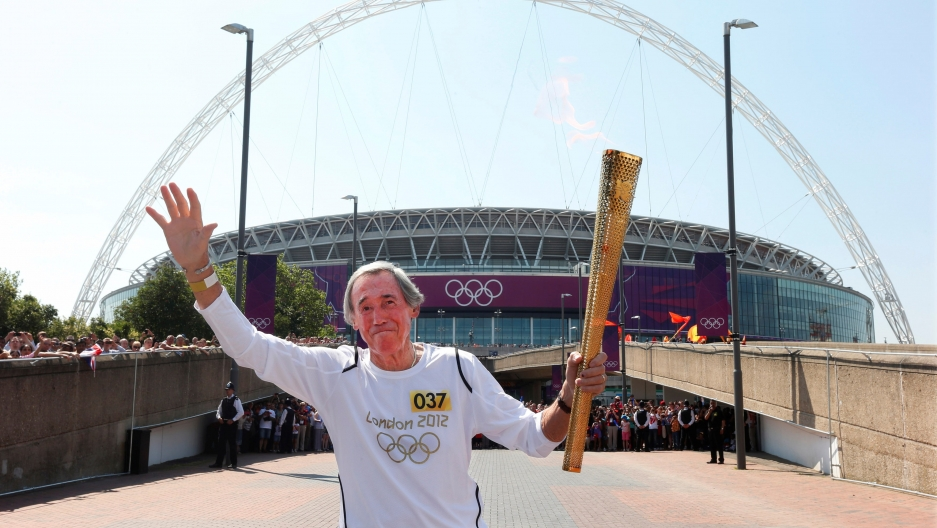 Gordon Banks runs with his arms up, one holding the olympic torch