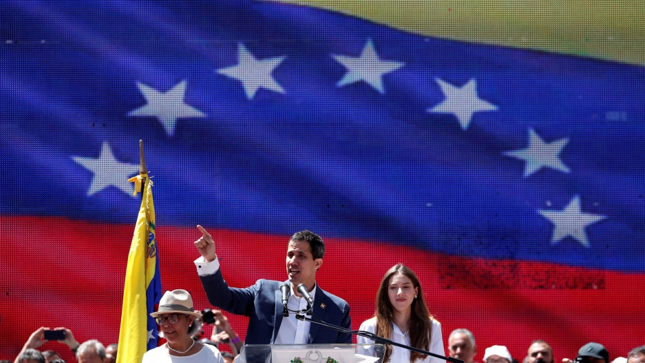 Opposition leader Juan Guaido is shown standing at a podium with a large Venezuelan flag projected behind him.