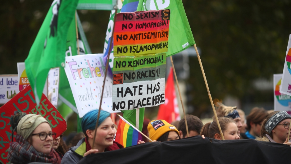 People are shown protesting against hate carrying flags and a brightly colored placard.