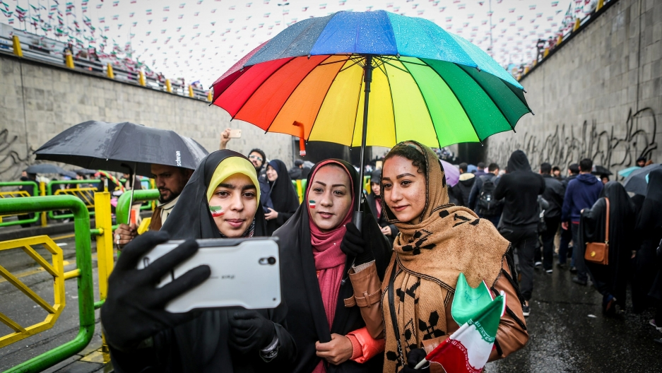 three women take a selfie with a rainbow umbrella covering them from the rain