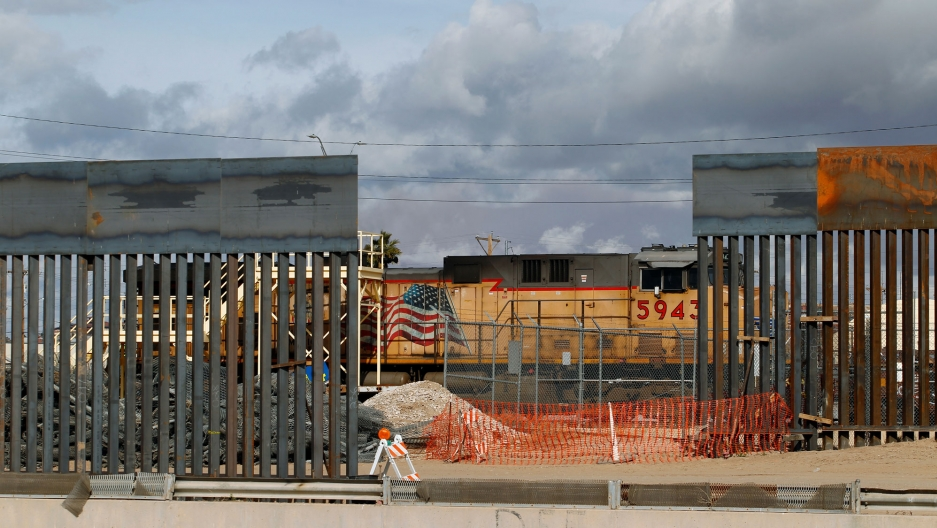 A view showing a section of a metal-slated border fence with a train rolling past in El Paso, Texas, as seen from Ciudad Juarez, Mexico.