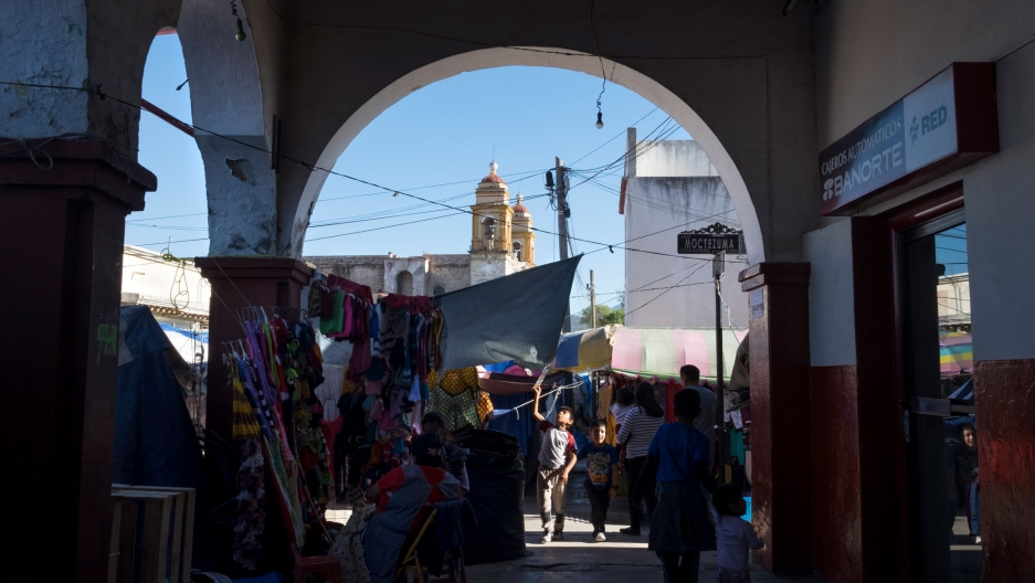 People are shown walking around at Tlaxiaco's market, with the steeples of the Santa Maria de la Asunción church in the distance.